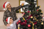 Son and dad decorating the christmas tree — Stock Photo