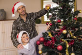 Smiling son and dad decorating the christmas tree — Stock Photo