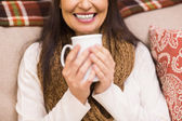 Mid section of a brunette enjoying a hot drink at christmas — Stock Photo