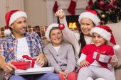 Festive family wearing santa hat on the couch — Stok fotoğraf