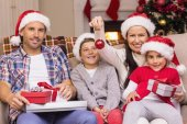 Happy family wearing santa hat on the couch — 图库照片