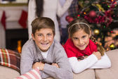 Brother and sister leaning on the couch — Stock Photo