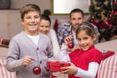 Smiling brother and sister holding gift and baubles — Stok fotoğraf