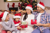 Festive family in santa hat exchanging gifts — Stock Photo