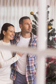 Smiling couple hugging near the christmas tree — Stock Photo