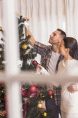 Love couple decorating the christmas tree together — 图库照片