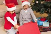 Surprised brother and sister opening a gift — Stock Photo