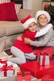 Brother and sister hugging near gifts  — Stock Photo