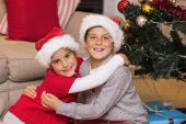 Smiling brother and sister hugging near the christmas tree — Stock Photo