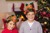 Happy brother and sister in headband near christmas tree — Stock Photo