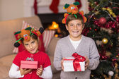 Brother and sister in headband holding gift — Stock Photo