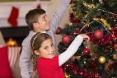 Brother and sister decorating the christmas tree together — Stockfoto