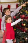 Smiling brother and sister decorating the christmas tree — Stockfoto