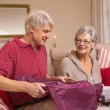 Senior couple opening a christmas present on sofa — Stock Photo #60886067