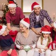 Happy extended family in santa hat holding gifts — Stock Photo #60886151