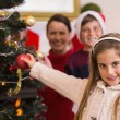 Smiling little girl decorating the christmas tree — Stock fotografie #60886327