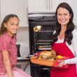 Happy mother and daughter posing with roast turkey — Stock Photo #60886833