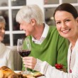 Portrait of woman toasting at camera during christmas dinner — Stock Photo #60886879