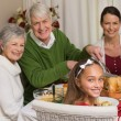 Smiling grandfather carving chicken during christmas dinner — Stock Photo #60886911