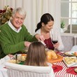 Happy grandfather carving chicken during christmas dinner — Stock Photo #60886915