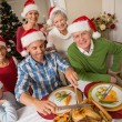 Father in santa hat carving chicken during christmas dinner — Stock Photo #60887443