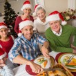 Father in santa hat carving chicken at christmas dinner — Stock Photo #60887445