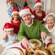 Grandfather in santa hat carving chicken at christmas dinner — Stock Photo #60887455
