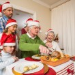 Grandfather in santa hat carving chicken at christmas — Stock Photo #60887461