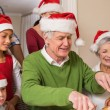 Grandfather in santa hat carving chicken at christmas dinner — Stock Photo #60887465
