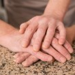 Senior couple holding hands on table — Stock Photo #60887679