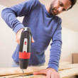 Casual man drilling hole in plank — Stock Photo #60888609