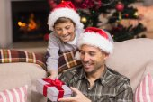 Son offering father a christmas gift on the couch — 图库照片