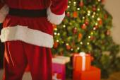 Mid section of santa standing in front of the christmas tree — Stock Photo