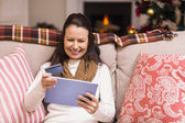 Festive brunette woman using her credit card and tablet pc — Stock Photo