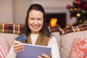 Brunette shopping online with laptop at christmas — Stock Photo