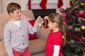 Brother and sister decorating the christmas tree with baubles — Stockfoto