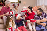 Multi generation family exchanging presents on sofa — Stock Photo