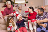 Multi generation family exchanging presents on couch — Stock Photo