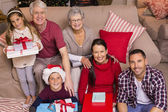 Happy family at christmas posing and holding gifts — Stock Photo