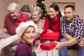 Smiling son exchanging gift with his family behind — Stock Photo