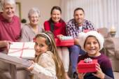 Brother and sister holding gift in front of their family — Stock Photo