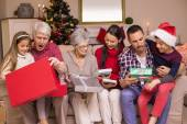 Multi generation family opening gifts on sofa — 图库照片