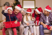 Festive multi generation family opening gifts together — Stock Photo