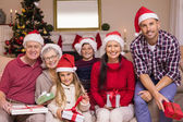 Multigeneration family wearing santa hats on the couch — Stockfoto