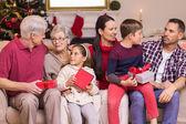 Multi generation family holding presents on sofa — Stock Photo