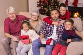 Multi generation family holding gifts on sofa — Stock Photo