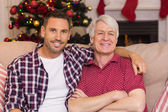 Father with arm around grandfather posing on sofa — Stock Photo