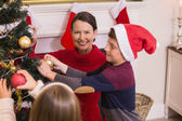 Mother son and daughter decorating the christmas tree — Stockfoto