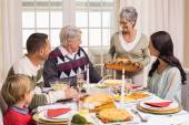 Grandmother holding turkey roast with family at dining table — Foto Stock