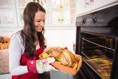 Smiling woman taking out her roast turkey — Stock Photo